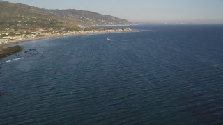 DCLA_170 - 5K stock footage aerial video fly over seagulls over the ocean and tilt to reveal Malibu, California