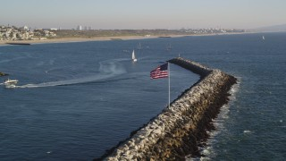 DCLA_186 - 5K stock footage aerial video flyby American flag on breakwater near sailboats and sport boats in Marina Del Rey, California