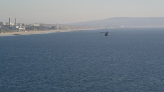 DCLA_188 - 5K stock footage aerial video track military helicopter to reveal the coastline in El Segundo, California