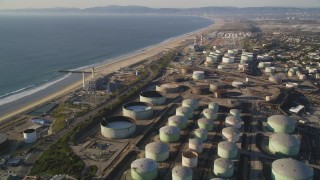 DCLA_195 - 5K stock footage aerial video fly over oil tanks at refinery to approach beach in El Segundo, California