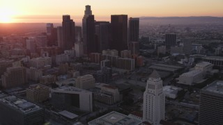 DCLA_242 - 5K stock footage video orbit and tilt from city hall to reveal skyline of Downtown Los Angeles at sunset, California