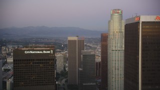 DCLA_263 - 5K stock footage aerial video fly between skyscrapers to approach US Bank Tower at twilight in Downtown Los Angeles, California