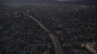DCLA_268 - 5K stock footage aerial video of tilting up heavy traffic on Highway 101 by Echo Park at twilight, California