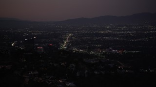 DCLA_283 - 5K stock footage aerial video of Universal City office buildings seen from Hollywood Hills at night, California