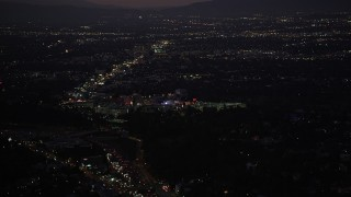 DCLA_284 - 5K stock footage aerial video tilt from Highway 101 traffic to reveal Universal City at night, California