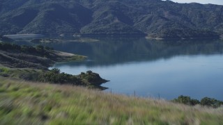 DCSF01_005 - 5K stock footage aerial video Flying low over grassy hill, revealing Lake Casitas, Ventura, California