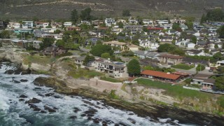 DCSF02_012 - 5K stock footage aerial video Flying by oceanfront homes and waves crashing on rocky shore, Shell Beach, California