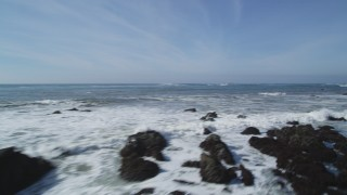 DCSF02_017 - 5K stock footage aerial video Fly low over Pacific Ocean waves and rocks, pan to reveal coastal cliffs, Avila Beach, California