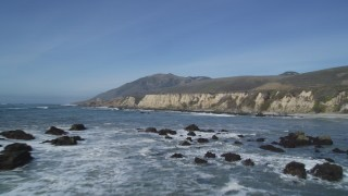 DCSF02_018 - 5K stock footage aerial video Fly over waves crashing against rocks and by coastal cliffs, Avila Beach, California