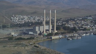 DCSF03_001 - 5K stock footage aerial video Flying by Dynegy Morro Bay power plant, eclipsed by Morro Rock, Morro Bay, California