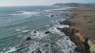 DCSF03_004 - 5K stock footage aerial video Fly over coastal cliffs and empty beach, and tilt up to follow the coast, Estero Bay, California