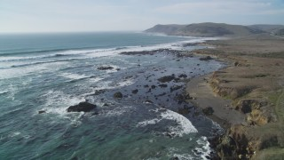 DCSF03_005 - 5K stock footage aerial video Fly over coastal cliffs and crashing waves of the Pacific Ocean, Estero Bay, California