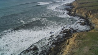 DCSF03_009 - 5K stock footage aerial video Tilt from crashing waves to coastline to reveal coastal cliffs, Cambria, California