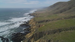 DCSF03_010 - 5K stock footage aerial video Flying over coastal cliffs by green hills, Cambria, California