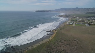 DCSF03_015 - 5K stock footage aerial video Tilt to reveal ocean waves rolling into the coast, San Simeon, California