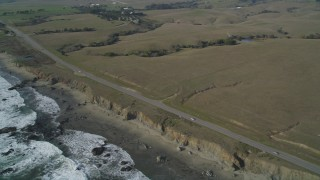 DCSF03_016 - 5K stock footage aerial video Flyby Highway 1 on the California coast and pan left to ocean waves and an empty beach, San Simeon, California
