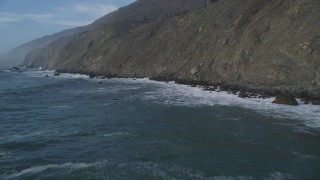 DCSF03_026 - 5K stock footage aerial video Fly low and pan across ocean waves crashing into cliffs, San Simeon, California