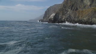 DCSF03_030 - 5K stock footage aerial video Fly low over ocean waves, rocks, by coastal cliffs, San Simeon, California