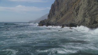 DCSF03_031 - 5K stock footage aerial video Fly low altitude over ocean waves, rocks, by coastal cliffs, San Simeon, California