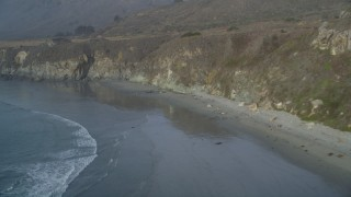 DCSF03_040 - 5K stock footage aerial video Fly over deserted beach at the base of cliffs, Big Sur, California