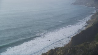 DCSF03_046 - 5K stock footage aerial video Tilt to bird's eye of ocean waves rolling toward cliffs, Big Sur, California