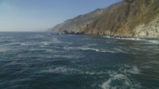DCSF03_050 - 5K stock footage aerial video Flying low over the Pacific Ocean, pan to coastal cliffs, Big Sur, California