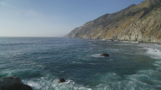 DCSF03_052 - 5K stock footage aerial video Fly low over Pacific Ocean to approach coastal cliffs, Big Sur, California