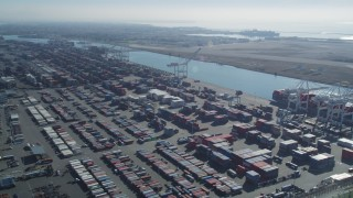 DCSF05_076 - 5K stock footage aerial video Flyby cargo containers to ships docked under cranes, Port of Oakland, Oakland, California