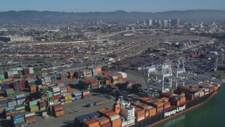 DCSF05_078 - 5K stock footage aerial video Flying by cargo cranes, shipping containers, cargo ships, Port of Oakland, Oakland, California