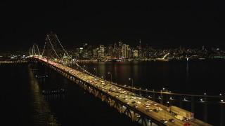 DCSF06_033 - 5K stock footage aerial video Flying by heavy Bay Bridge traffic, Downtown San Francisco skyline in background, California, night