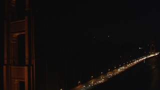 DCSF06_041 - 5K stock footage aerial video Tilt up from traffic and fly by Golden Gate Bridge, San Francisco, California, night