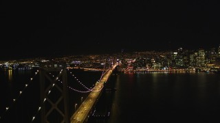 DCSF06_086 - 5K stock footage aerial video Reverse fly over Bay Bridge with skyline in background, Downtown San Francisco, California, night