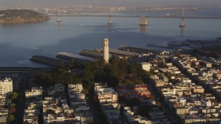 DCSF07_008 - 5K stock footage aerial video Approach Coit Tower with Bay Bridge in background, North Beach, San Francisco, California, sunset