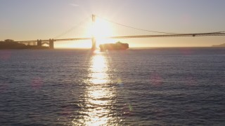 DCSF07_036 - 5K stock footage aerial video Low approach to a cargo ship near Golden Gate Bridge, San Francisco, California, sunset