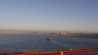DCSF07_038 - 5K stock footage aerial video Cargo ship sailing the bay, Golden Gate Bridge, skyline in the distance, San Francisco, California, sunset