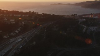 DCSF07_051 - 5K stock footage aerial video Pan across Highway 101 in Presidio, reveal Golden Gate Bridge, San Francisco, California, sunset