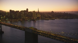 DCSF07_099 - Aerial stock footage of 5K Aerial Video Reverse view of Bay Bridge and Downtown San Francisco skyline, California, twilight