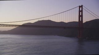 DCSF10_039 - Aerial stock footage of 5K Aerial Video Fly low to approach Golden Gate Bridge, pan to reveal a cargo ship, San Francisco, California, twilight