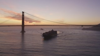 DCSF10_041 - Aerial stock footage of 5K Aerial Video Track cargo ship sailing by the Golden Gate Bridge, San Francisco, California, twilight