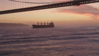 DCSF10_043 - Aerial stock footage of 5K Aerial Video Track oil Tanker approaching Golden Gate Bridge, San Francisco, California, twilight