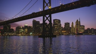 DCSF10_065 - Aerial stock footage of 5K Aerial Video Fly low beneath Bay Bridge with a view of the Downtown San Francisco skyline, California, twilight