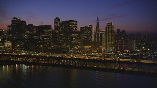 DCSF10_074 - Aerial stock footage of 5K Aerial Video Fly by heavy traffic crossing the Bay Bridge with the skyline in background, Downtown San Francisco, California, night