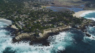 DCSF11_010 - Aerial stock footage of 5K Aerial Video Waves crashing into rocks by a coastal neighborhood in Carmel, California