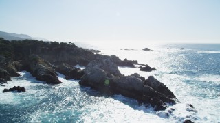 DCSF11_014 - Aerial stock footage of 5K Aerial Video Flying by ocean waves crashing into coastal rock formations, Carmel, California