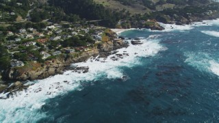 DCSF11_016 - Aerial stock footage of 5K Aerial Video Flyby waves crashing below coastal homes and tilt up to the coastline, Carmel, California