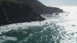 DCSF11_022 - Aerial stock footage of 5K Aerial Video Tilt from ocean waves to reveal tall coastal cliffs, Big Sur, California