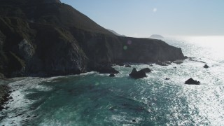 DCSF11_023 - Aerial stock footage of 5K Aerial Video Flying by waves crashing into the base of coastal cliffs, Big Sur, California