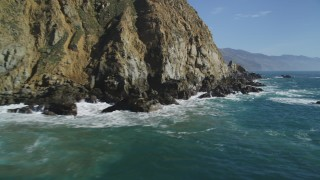 DCSF11_031 - Aerial stock footage of 5K Aerial Video Fly low over waves slamming into coastal cliffs, Big Sur, California