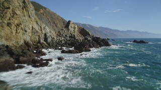 DCSF11_032 - Aerial stock footage of 5K Aerial Video Flying over waves crashing into rocks at the base of cliffs, Big Sur, California