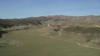 DFKSF01_007 - 5K stock footage aerial video of flying over a hill, revealing isolated ranch house and barn, Simi Valley, California